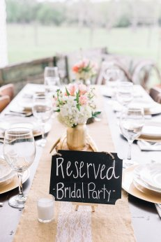 Bridal Party Table centerpieces inside gold mason jars filled with white hydrangea, white wax, coral roses, blush alstroemeria, and white stock, on top of log slices with antlers to accent.