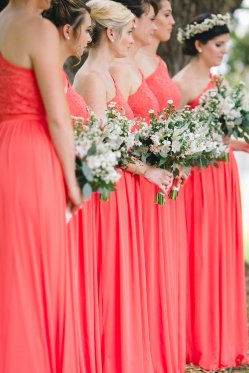 Samantha's Maid's in coral gowns with bouquets filled with white monte casino, white alstroemeria, white wax flowers, white stock, white veronica, and seeded eucalyptus.
