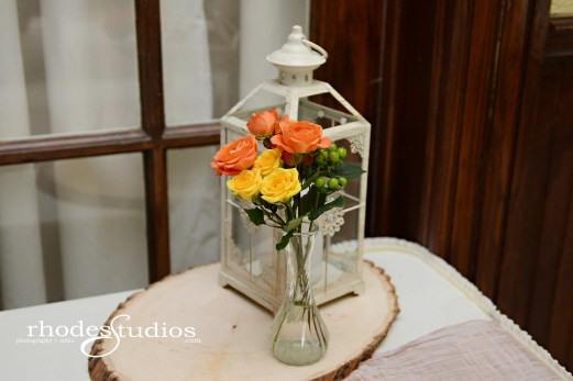 Green jade hypericum, golden galaxy spray roses, and orange babe spray roses in a clear bud vase.