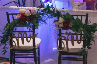 Chair sashes with red freedom roses, white tibet roses, ester roses, greens, and red ranunculus.