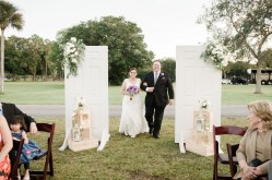 Bride and her father walking down the aisle through our white ceremony doors.