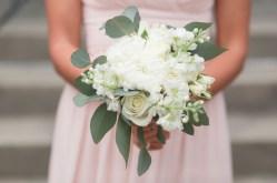 Bridesmaids bouquet using white football mums, white ranunculus, white stock, white tibet roses, silver dollar eucalyptus, and white majolika spray roses.