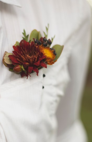 Grooms boutonniere of burgundy and yellow mums with greens and hypericum berries.