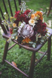 Brides bouquet created with yellow and burgundy mums, purple snap dragons, hypericum berries, proteas, ivory standard roses, and greens.