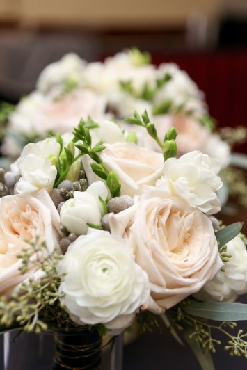 Brides maids bouquets with freesia, white ranunculus, brunia, and O'hara garden roses