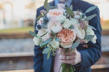 Brides bouquet with thistle, garden roses, ranunculus, seeded eucalyptus, and spray roses.