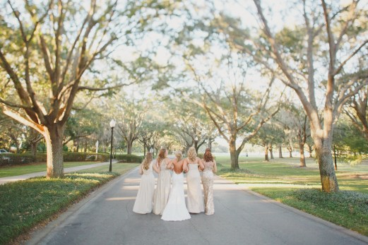 Champagne colored bridesmaids dresses with the bride walking down the road