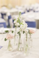 Simple centerpieces of bud vases with white and blush floral for half of the tables.