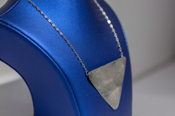 Rhodium Triangular Necklace side view on a blue display element.