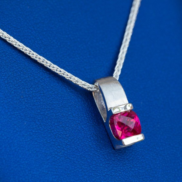 Pink Topaz Pendant angle view on a blue background.