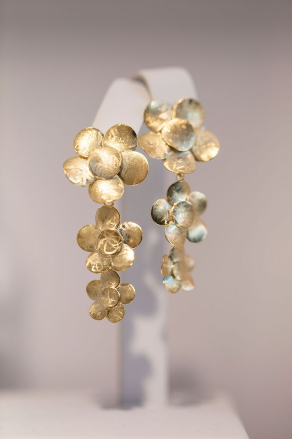 18KY Plated Triple Flowers Earrings on an element in showroom.