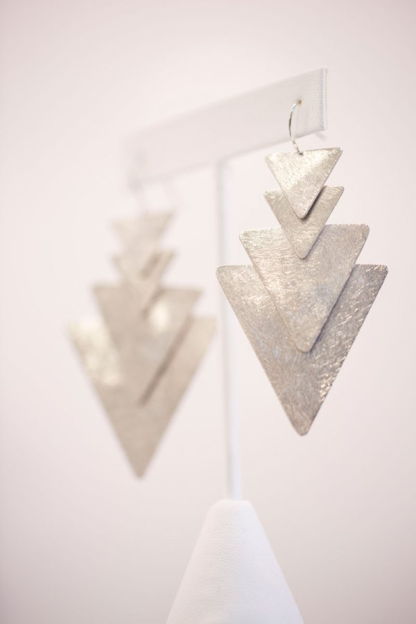Rhodium Plated 4 Triangle Dangle Earrings on an element in showroom.