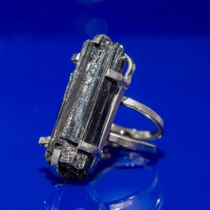 Rough Black Tourmaline Ring angle view on a blue reflective surface.
