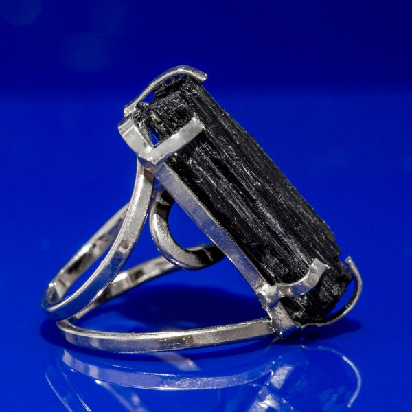 Rough Black Tourmaline Ring side view on a blue reflective surface.