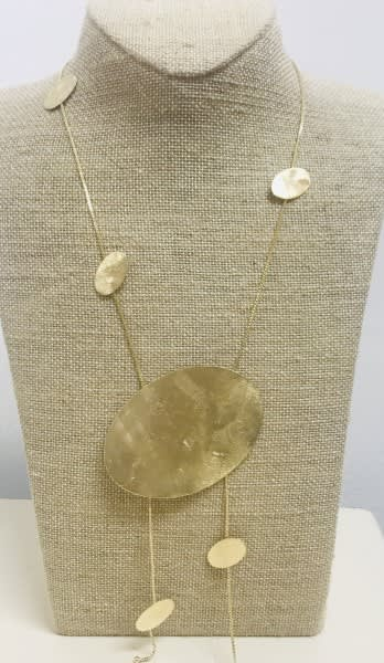 Yellow Gold Floating Ovals Necklace on a tan colored display element.