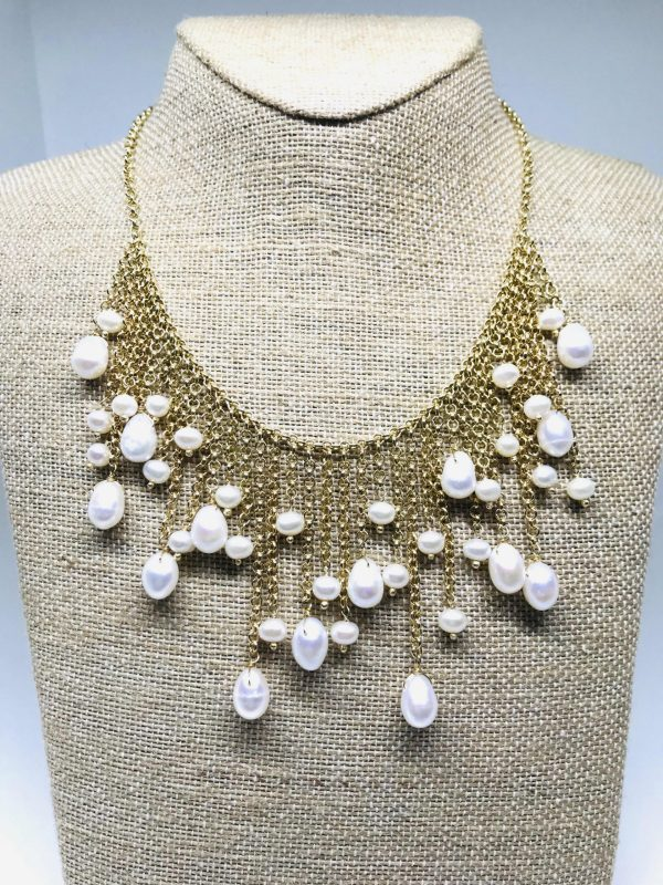 Yellow Gold Floating Pearl Dangles Necklace on a tan colored display element.