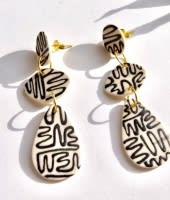 Squiggled Fangs Pebbles Porcelain Earrings laying on a white table.