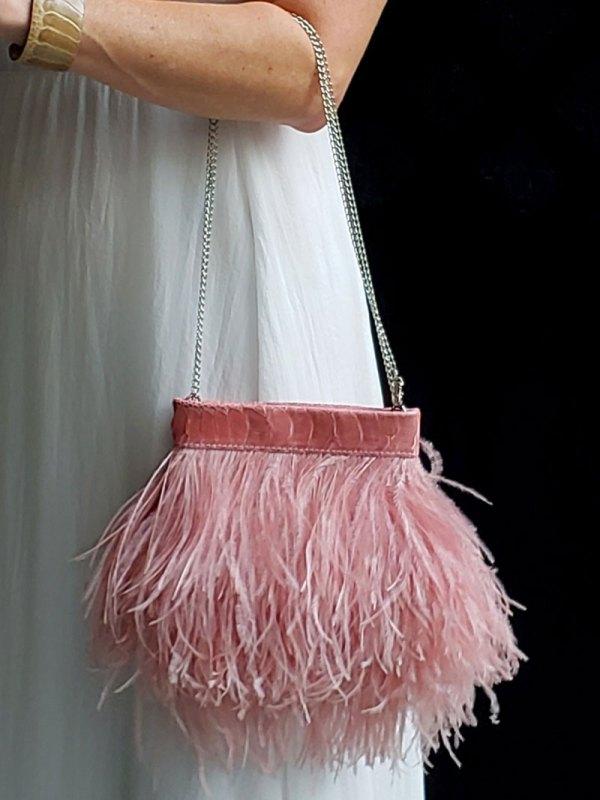 Blush Ostrich Feather Handbag held on a models arm.