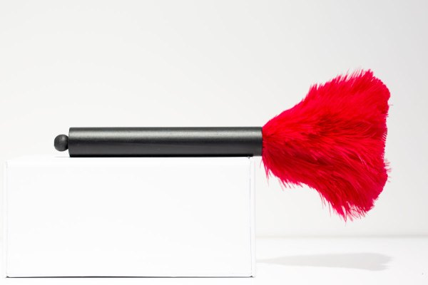 Pink Mini Ostrich Feather Duster laying on its side.