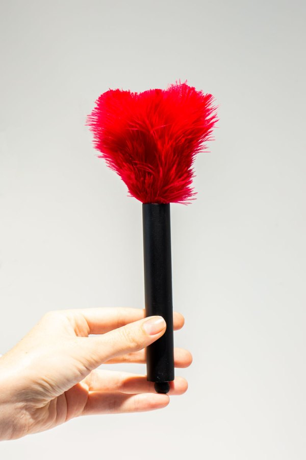 Pink Mini Ostrich Feather Duster held in a models hand.