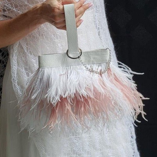 Photo of a model holding the pink and white kristen ostrich feather handbag.