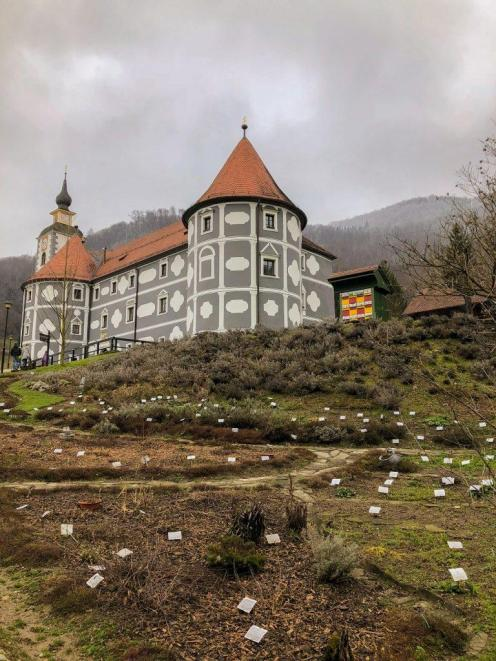 A herbal garden and grey monastery with orange roof