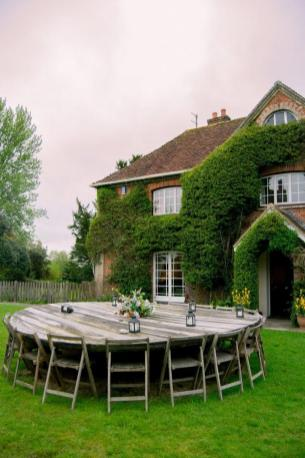 300 year old farmhouse covered with ivy, a round table with 12 chairs in the fronnt