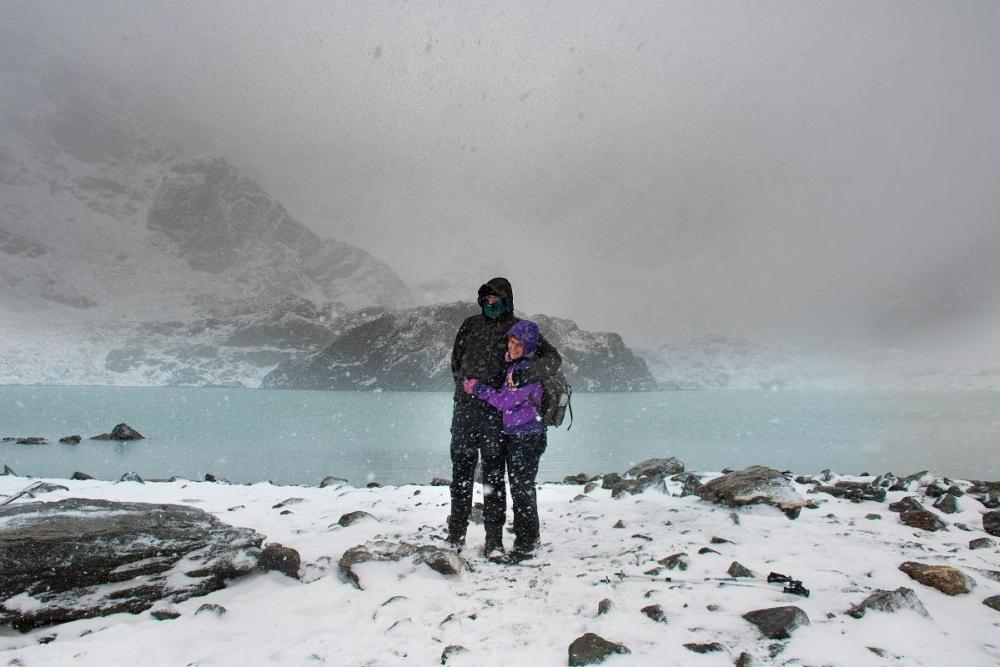 Us in the middle of the snowstorm, at the top of the mountain next to the glacial lake. (Hiking in Ushuaia)