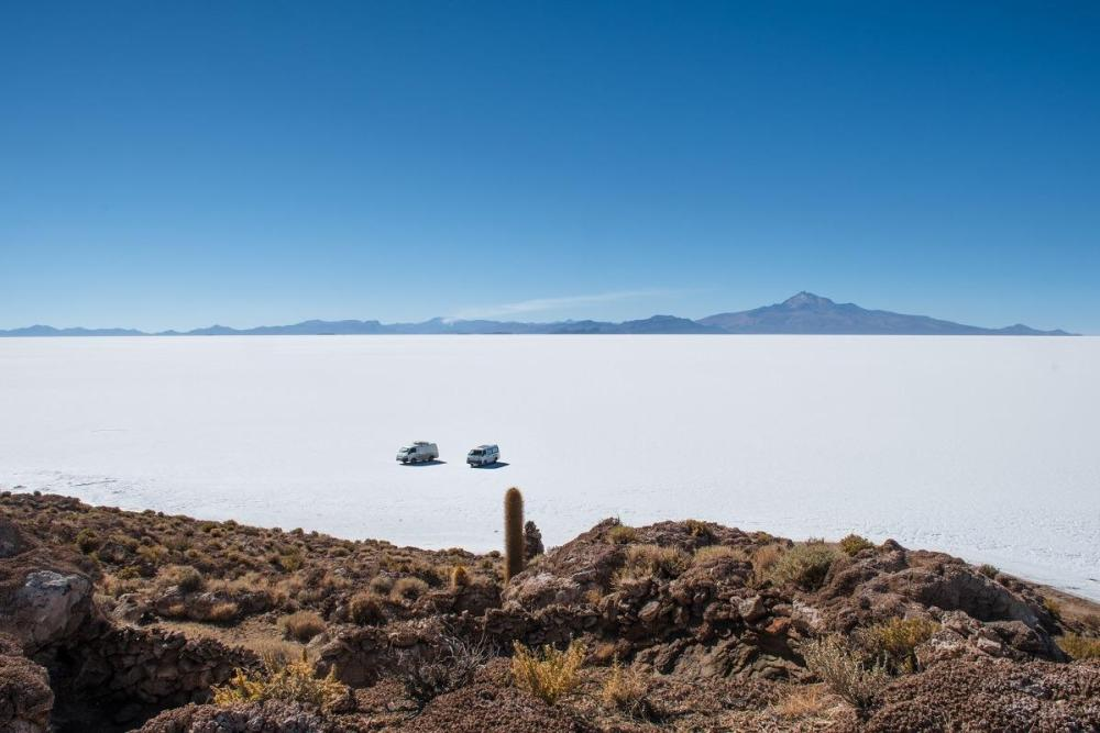 Two vans from the distance in a white desert of Salar de Uyuni, Bolivia