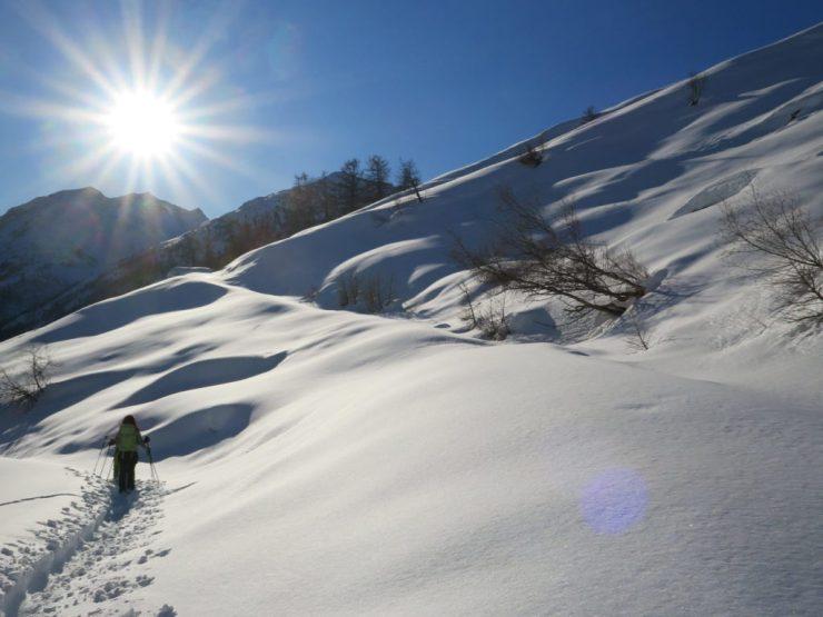Schneeschuhwanderer laufen der Sonne hinter den Gipfeln entgegen und hinterlassen eine Spur im Pulverschnee