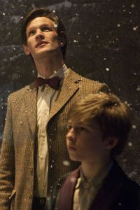 The Doctor (Matt Smith) and a child stand in the snow.