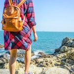 woman with backpack looking out over the ocean on holiday