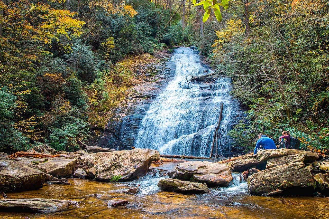 Couple relaxing on rocks at Helton Creek Falls near Helen, GA