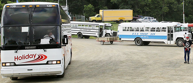 Old and the new:  Air-conditioned tour buses for transport from parking lots to the site and Boy Scout buses for additional help.