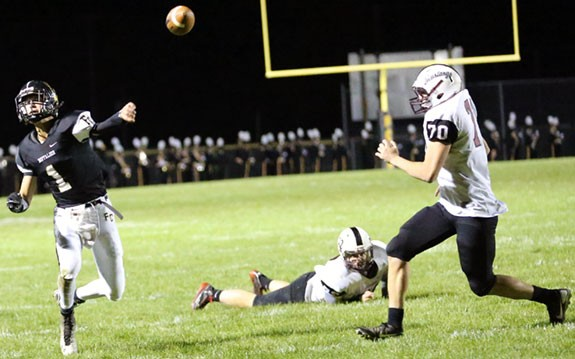 Brady Underwood evades rush to deliver pass. (Photos by Doug Thompson)