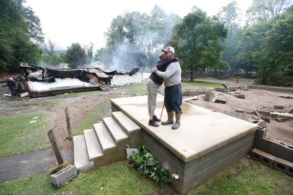 Jimmy Scott gets a hug from Anna May Watson as they clean up from severe flooding in White Sulphur Springs in West Virginia on Friday. (Steve Helber/AP)
