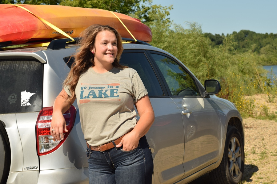 model wearing Go Jump in a Lake t-shirt and smiling by her SUV and kayak