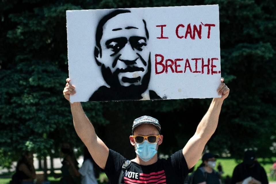 """A protester carrying the image of George Floyd on May 30 2020 in Denver, Colorado, together with his last words: """"I can't breathe"""" - Jason Connolly / ©AFP"""