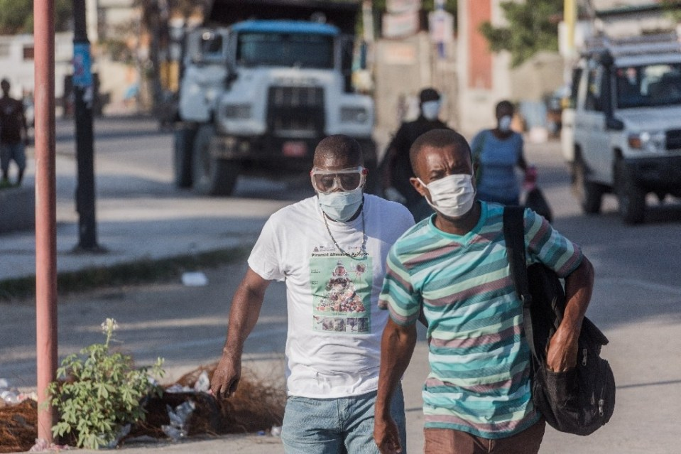 """""""Two men wear masks as they walk in the streets of downtown Port-au-Prince on March 26, 2020. When the novel coronavirus first appeared in Haiti authorities and humanitarian experts panicked, worried about the country's decrepit health system -- but health officials say the virus may have already passed its peak - Pierre Michel Jean / ©AFP"""""""