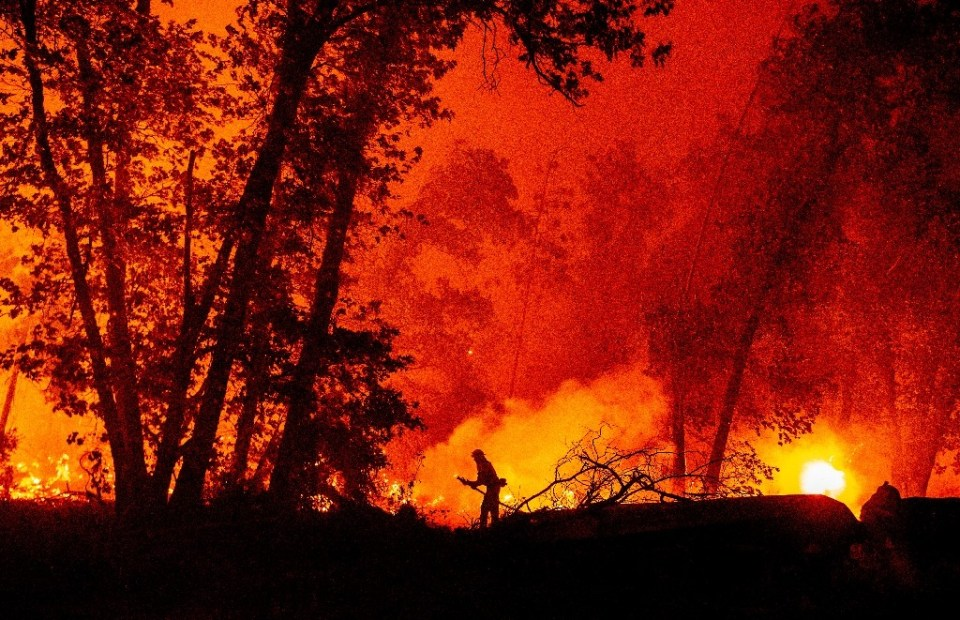 A firefighter douses flames as they push towards homes during the Creek Fire in the Cascadel Woods area of unincorporated Madera County, California on September 7, 2020 - JOSH EDELSON / ©AFP