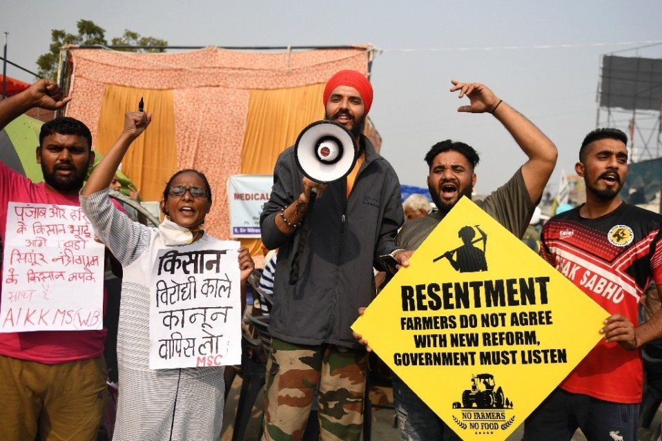 Farmers hold placards and shout slogans during a protest at the Delhi-Haryana state border - Money SHARMA / ©AFP