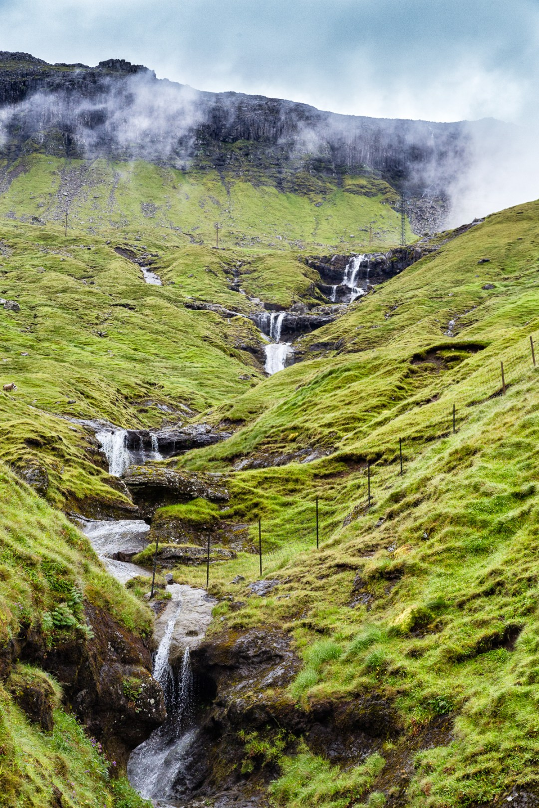 Waterfall is right before the tunnel near Kaldbaksbotnur, Faroe Islands by Jon Armstrong for Blurbomat.com.
