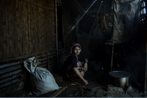 Say Tha Mar Gyi, Myanmar, 2015: A. cooks in her family home in Say Tha Mar Gyi Camp. She is married, but her husband left her within the last year to return to his family. ©Lynsey Addario