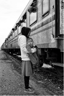 Slovenia, 2015: After arriving by train at Središče ob Dravi, Slovenia, a mother and baby wait for buses provided by the Slovenian authorities to take them further along their journey towards Western Europe. ©Tom Stoddart