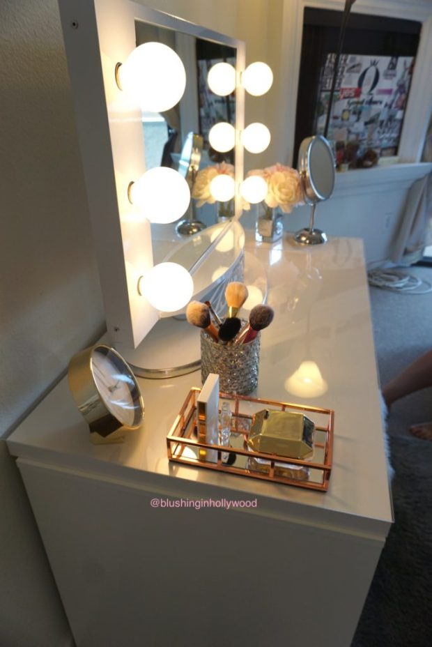 Side view of my vanity where you can see my Vanity Girl Hollywood Lighted Mirror, a rose gold perfume tray, my mercury glass candle holder that I put makeup brushes in, faux peonies, and my Conair magnifying mirror.