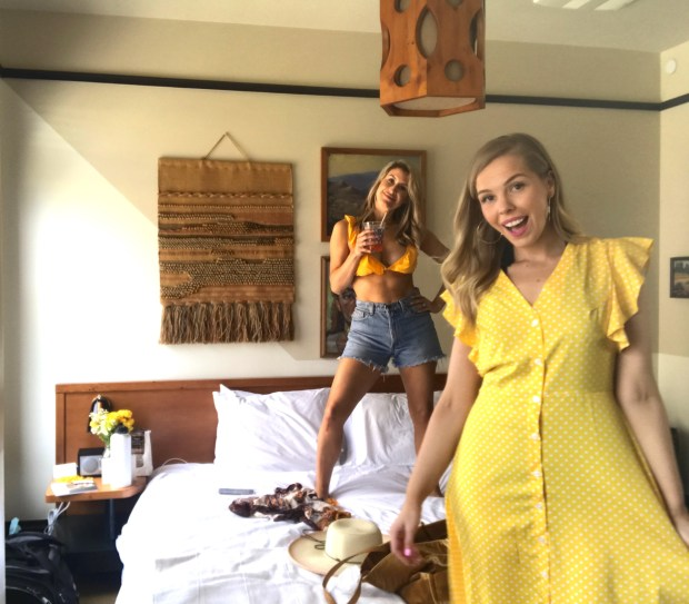 Me wearing a yellow polka dot short sleeve dress at the Freehand Los Angeles Hotel with Jessica Jay in a yellow bikini on the bed