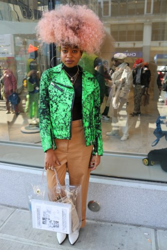 FIT student Tylisa Curry captured for FIT's Blush Magazine online street style column. Tylisa is sporting a lime green snakeskin leather jacket, black stripped shirt, tan cargo trousers, white booties and clear tote bag.