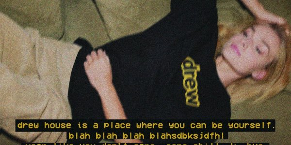 Image of girl wearing a black Drew tee shirt with the writing, Drew house is a place where you can be yourself. Blah blah blah blahsdbksjdfhl. Wear like you don't care. Come chill. K bye.""