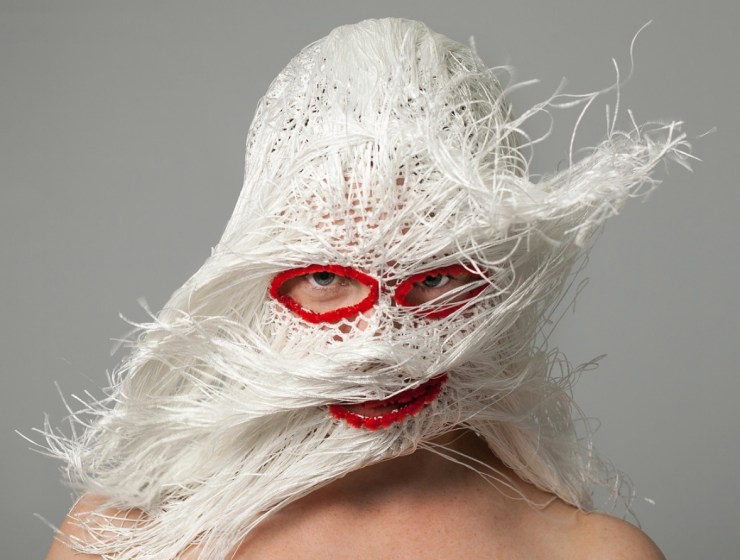 Balaclava Mask with white yarn fringe in motion, and red eye and mouth outline