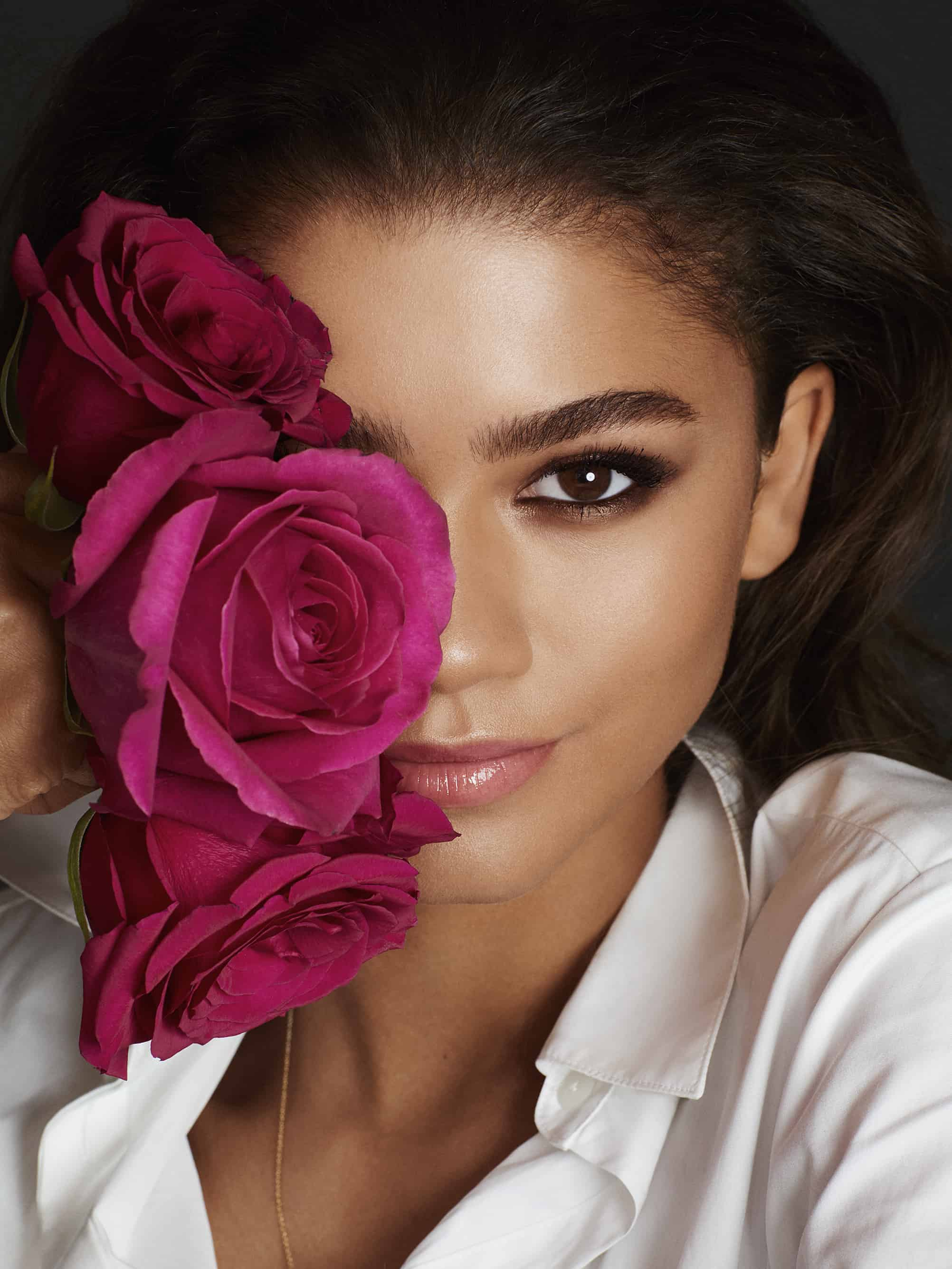 Headshot of Zendaya with pink roses covering half of her face